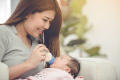 Lait de alimentation de mère asiatique de bouteille de lait à la fille de bébé photos libres de droits
