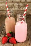Lait de fraise et chocolaté dans des bouteilles sur le bois Image libre de droits