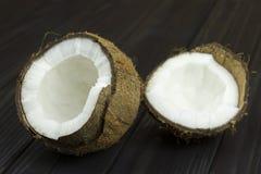 Lait de noix de coco organique blanc brun tropical frais de pulpe de noix de coco sur le fond noir en bois Photographie stock libre de droits
