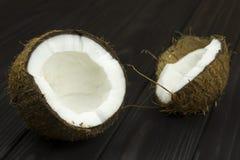 Lait de noix de coco organique blanc brun tropical frais de pulpe de noix de coco sur le fond noir en bois Photo libre de droits