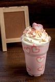Lait de poule rose avec des marshmellows de forme de coeur complétant sur en bois Images stock