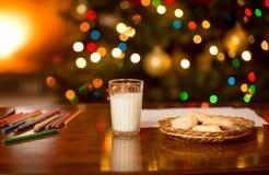 Lait et biscuits attendant Santa Claus au réveillon de Noël Photos stock