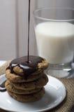 Lait et biscuits avec des puces et ganache d'un plat blanc Image stock