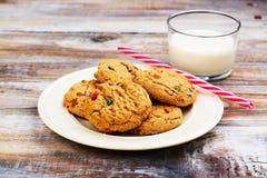 Lait et biscuits chapeau pour de Santa Claus et de Santa ` s au-dessus de CCB en bois Photos stock
