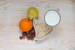Lait, fruit, écrous, poire et orange de petit déjeuner Photographie stock