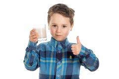 Lait potable d'amande de garçon avec des pouces  Image libre de droits