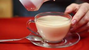 Lait se renversant de fille dans le thé noir Vrai gourmet Préparation de boisson savoureuse banque de vidéos