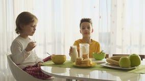 Lait se renversant de garçon dans le plat avec des flocons d'avoine, deux frères prenant le petit déjeuner clips vidéos