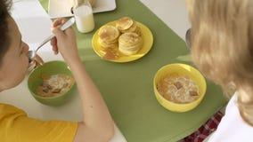 Lait se renversant de garçon dans le plat avec des flocons d'avoine, deux frères prenant le petit déjeuner banque de vidéos