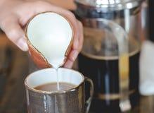Lait se renversant de jeune femme dans la tasse de café filtré Image stock