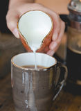 Lait se renversant de jeune femme dans la tasse de café filtré Photo libre de droits