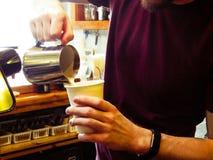 Lait se renversant de travailleur de café dans la tasse de café images stock