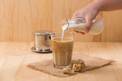 Lait se renversant dedans au verre de café sur une table en bois image stock