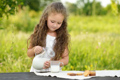 Lait se renversant mignon de petite fille dans de verre ayant l'été extérieur de petit déjeuner image stock