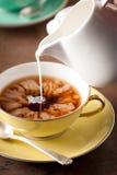 Lait se renversant sur une tasse de thé Photo stock