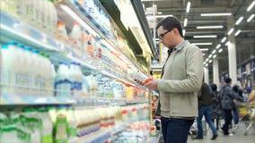 Laitages de achat d'homme dans le supermarché banque de vidéos