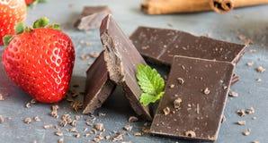 Laiterie et chocolat amer avec des fraises et des feuilles en bon état Photo libre de droits