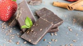 Laiterie et chocolat amer avec des fraises et des feuilles en bon état Image stock