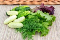 Laitue de feuille multicolore, concombres, aneth sur une serviette en osier préparée pour couper en tranches la salade photo libre de droits