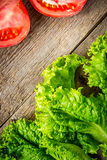 Laitue et tomates sur le vieux conseil Images stock