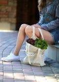 laitue Le sac de toile complètement de la salade fraîche se tient près des jambes de la femme élégante Photos libres de droits