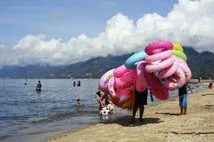 Young man sells and peddles ring lifebuoy on white sand beach. Laiya, San Juan, Batangas, Philippines - May 28, 2017: Young man sells and peddles ring lifebuoy Stock Photos