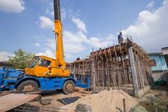 Laje de cimento da carcaça do trabalhador com o guindaste móvel para construir uma casa Imagens de Stock