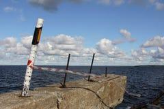 Laje de cimento velha com barras de metal e marco miliário no litoral Fotos de Stock Royalty Free