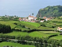 Lajes das Flores, Flores island, The Azores. View of Lajes das Flores across a road and patchwork of green fields with a headland and the sea behind stock image
