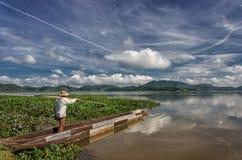 LAK VIET NAM DE DAK: El grupo de granjero asiático va a trabajar en barco de fila en el lago en tiempo del otoño, familia de mino imágenes de archivo libres de regalías