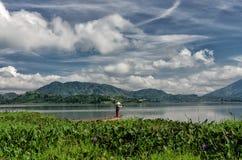 LAK VIET NAM DE DAK: El grupo de granjero asiático va a trabajar en barco de fila en el lago en tiempo del otoño, familia de mino imagen de archivo