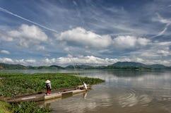 LAK VIET NAM DE DAK: El grupo de granjero asiático va a trabajar en barco de fila en el lago en tiempo del otoño, familia de mino imagenes de archivo