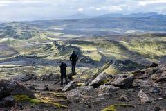 看火山的风景的两个远足者在Lakagigar,拉基火山火山口,冰岛 免版税库存照片