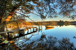 Lake. Autumn at the lake with a rowing boat at a pier Stock Image