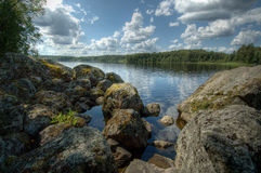 Lake. Stones on the shore of Lake. Clouds Royalty Free Stock Images