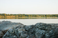 Lake. Sky, stone and green trees in nature over lake with reflections Royalty Free Stock Images
