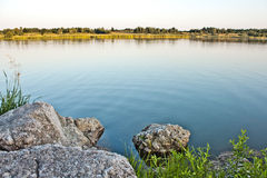 Lake. Sky, stone and green trees in nature over lake with reflections Royalty Free Stock Photography
