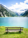 At the lake. Old wooden bench at a lake in austria (zillertal Stock Image