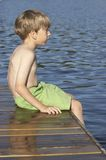 Lake. Boy sitting on wharf Stock Image