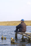 In the lake. Quiet place for the reflections and leisure, men sits on the bridge in lake and about which that he thinks Royalty Free Stock Photo