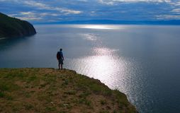 Lake. Calm Baikal lake, surrounded by mountains, human staying on the coast Royalty Free Stock Photography