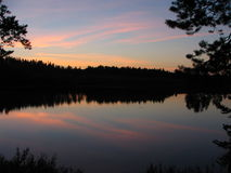 Lake. Night view of a lake. Pines in front, mainly spruce in background. Water is like a mirror Stock Photo