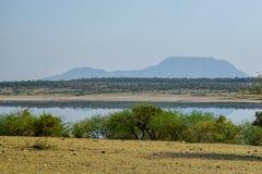 Lake against an arid landscape. Lake Magadi against an arid landscape, Magadi, Rift Valley, Kenya  safari travel scenic beautiful nature natural dry desert royalty free stock image