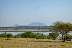 Lake against an arid landscape. Lake Magadi against an arid landscape, Magadi, Rift Valley, Kenya  safari travel scenic beautiful nature natural dry desert stock image