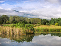 Lake against misty mountains Royalty Free Stock Photo