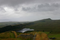 Lake along hadrians wall. A lake cliff and mountain along hadrian's wall with storm coming in stock photo