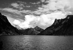 Lake and Alps mountains. Scenic black and white view of Austrian alps mountains and cloudscape with lake in foreground Stock Photos