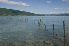 Lake Annecy. View of the lake of Annecy in french alps and the poles protecting reedbeds Stock Photos