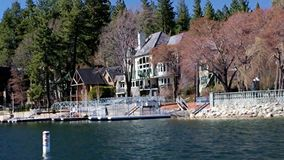 Lake Arrowhead Queen Boat Tour Celebrity Estates. Arrowhead Lake boat pan tour of Celebrity Mountain Resort Homes. Pan from Water of estates in California stock video