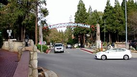 Lake Arrowhead Village Entrance wth Cars passing by. Arrowhead Lake Village shopping center entrance featuring cars at intersection passing by and entering stock footage